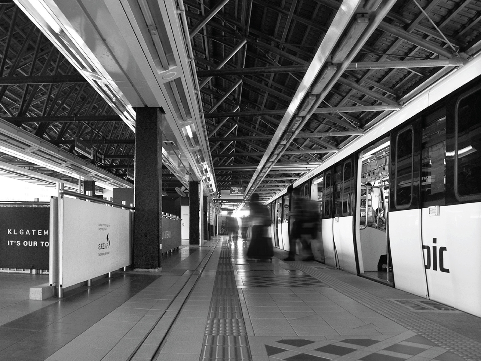 KL Gateway by Suezcap train station brand advertisement takeover on handrail panels with a stopped train that is allowing people to disembark in black and white visual